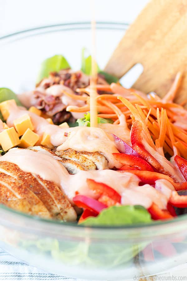 A chopped salad topped with shredded carrots, red pepper slices, avocado and cheddar cubes, bacon, tomatoes, and chicken is slathered in rich and creamy barbecue sauce.