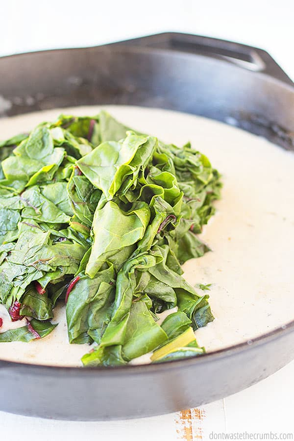 Vibrant and fresh Swiss Chard placed in a pool of delightful cream. The cast iron pan adding another layer of flavor.