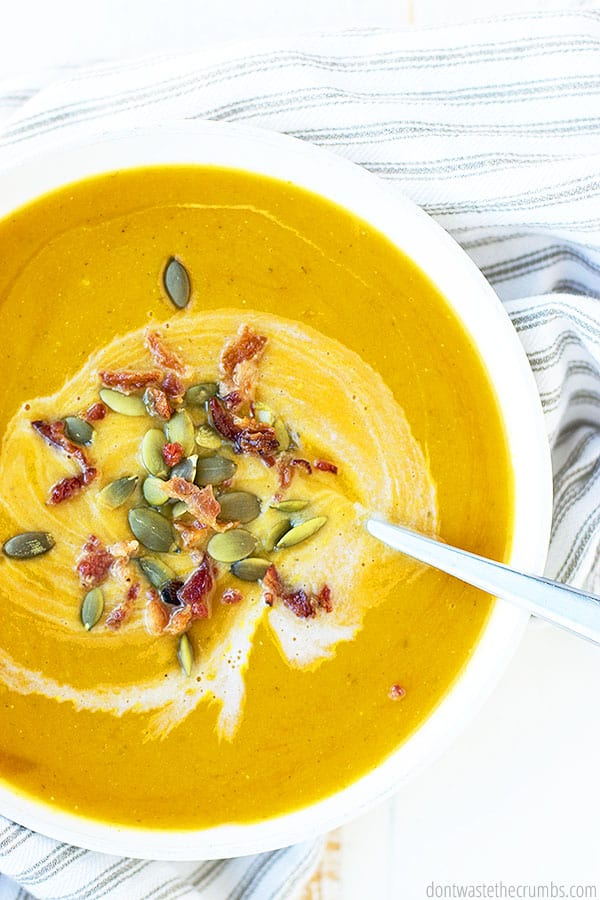 Butternut squash soup with a swirl of cream, topped with pumpkin seeds (pepitas) and crispy bacon bits. Delicious served with fresh homemade no knead artisan bread.