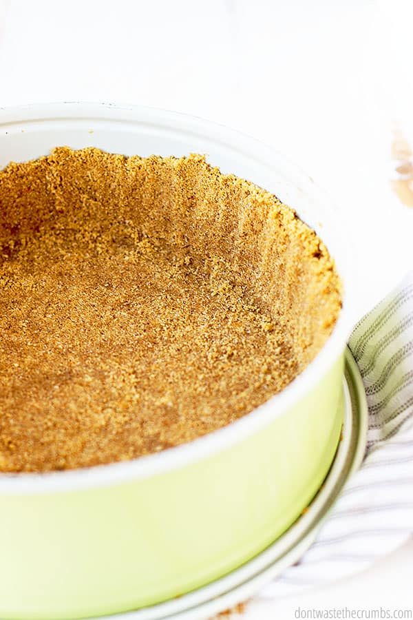 Shown is a wonderfully textured and crisp graham cracker crust in a pie pan set on patterned towel.