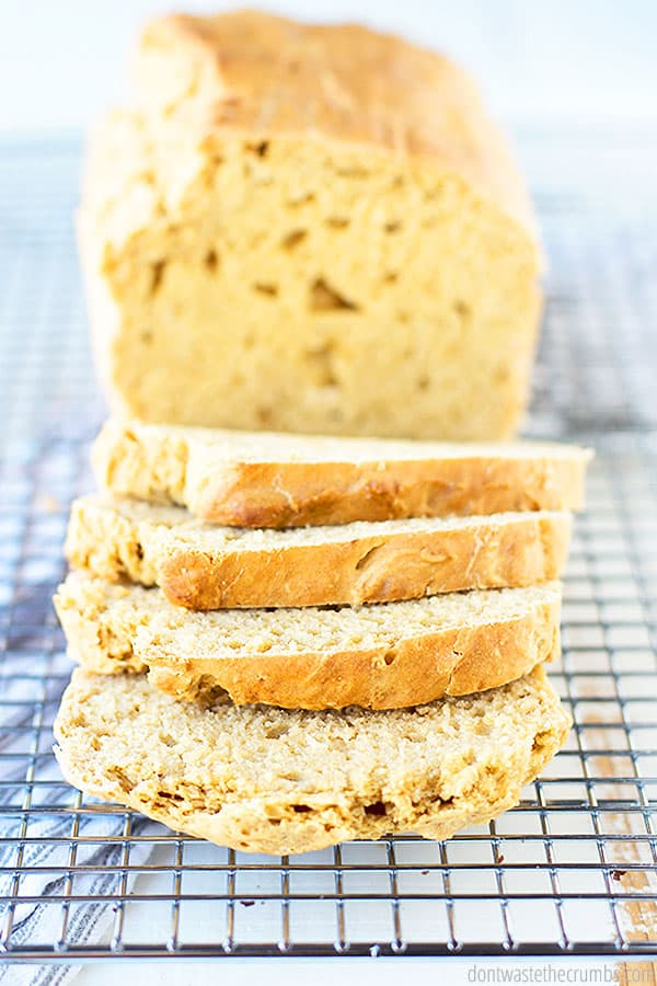 A loaf of fluffy and savory beer bread, 4 slices are cut off allowing us to see the delicious buttery and airy center.