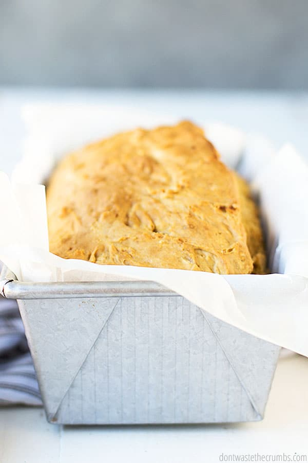 A silver loaf pan lined with parchment paper containing beautiful loaf of freshly baked beer bread.
