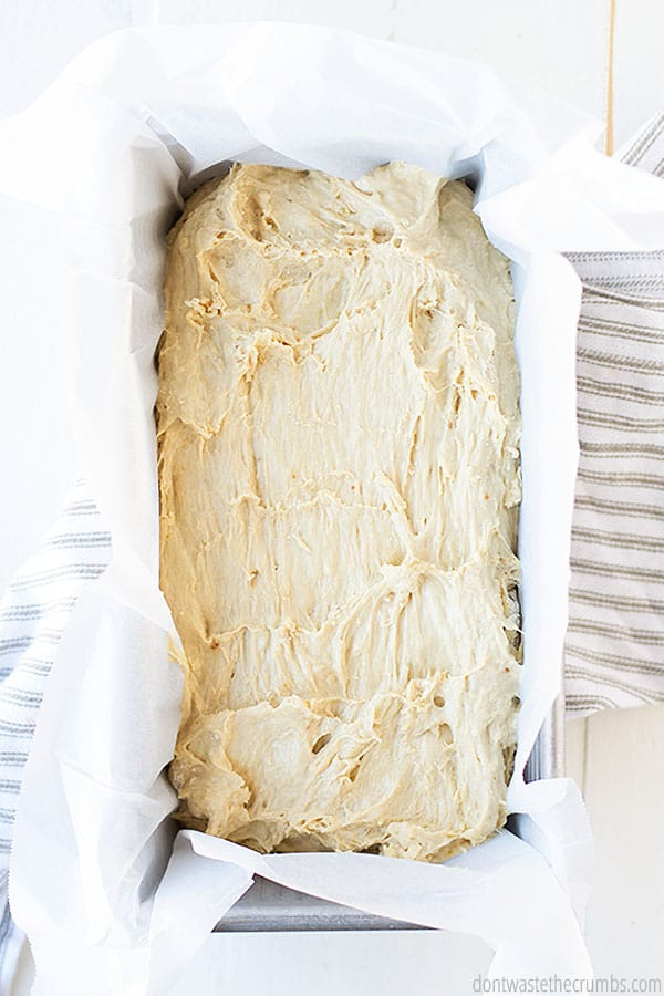 The raw dough in a loaf pan waiting to be cooked to perfection. The pan is set on a white table and striped towel.