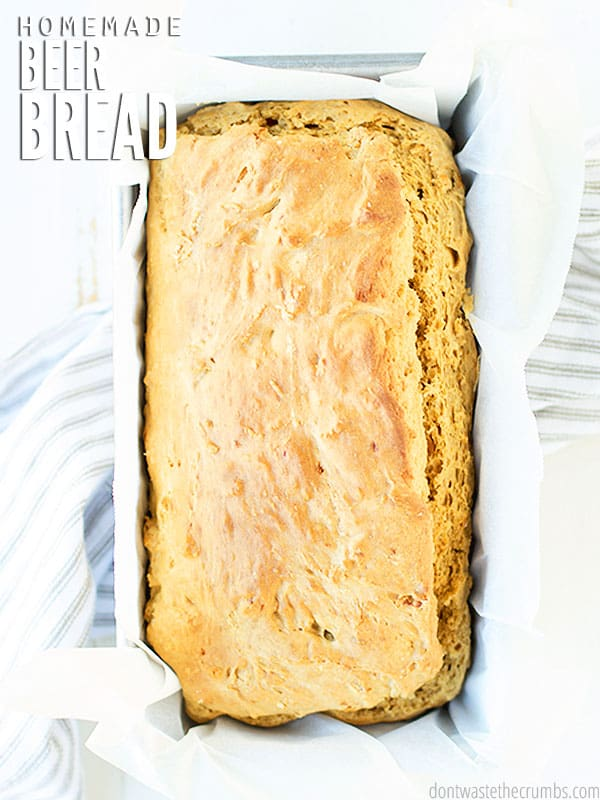 """A golden loaf of crisp and fluffy beer bread in a loaf pan that is lined with parchment paper. You can see the beautiful crust on the loaf of bread. Text overlay, """"Homemade Beer Bread"""""""