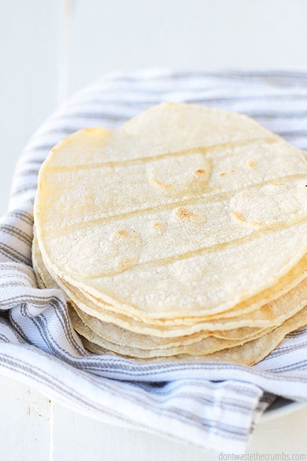 A stack of corn tortillas shown from the side. They are sitting on a striped towel waiting to devoured.