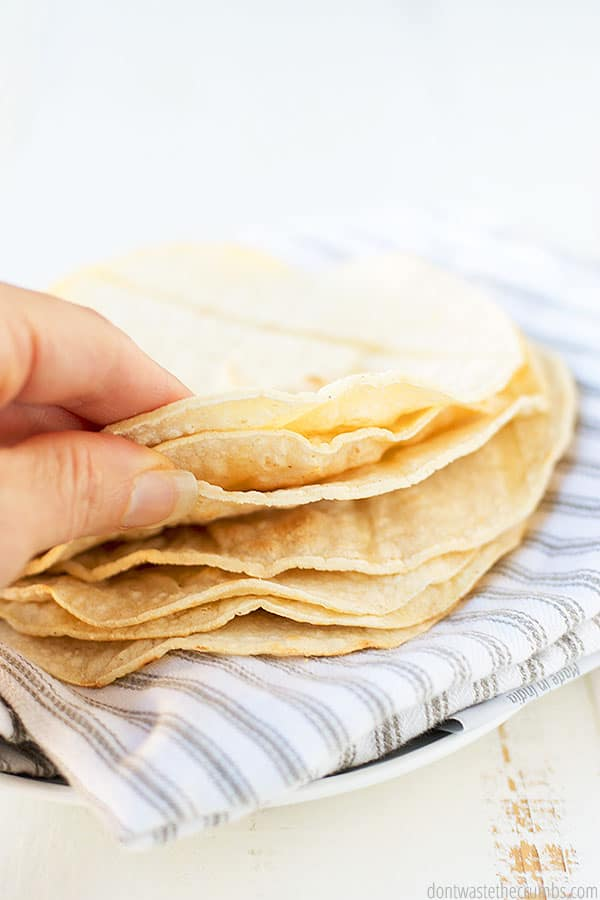 A hand taking three tortillas from a stack of 7. They are served on a towel with a plate underneath it.  With tortillas like this it is no wonder that taking three of them is a must.
