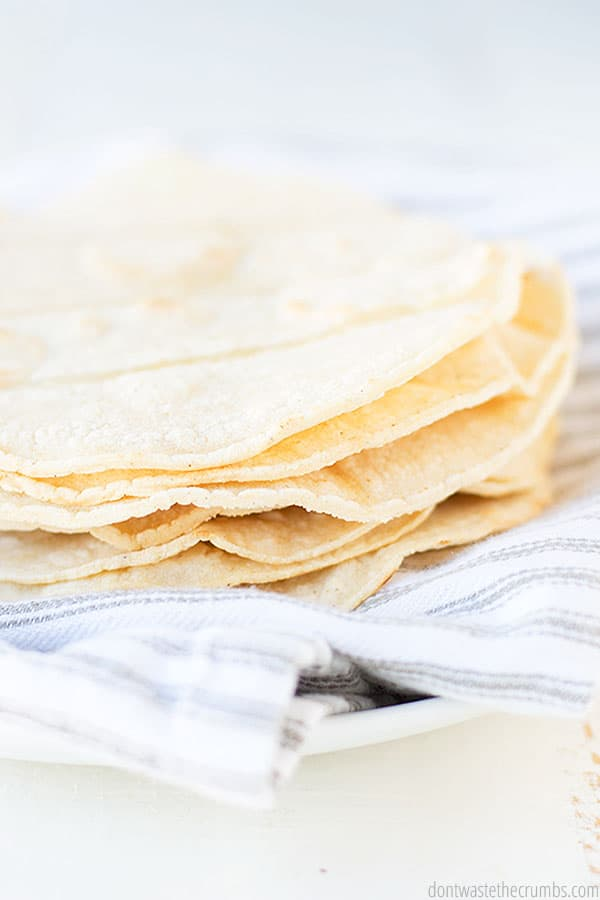 6 tortillas on a striped towel and white plate. These corn tortillas have amazing texture as well as robust flavor.