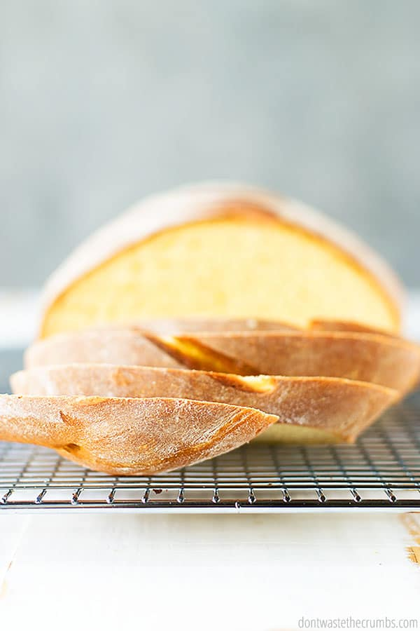 A half sliced loaf as seen from the side. The texture of the crust is visible. The bumps and crevasses of the crust look like the perfect bite of crisp and fluffy bread.