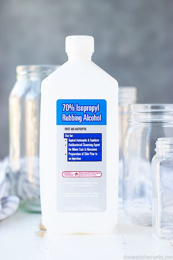 A towel and four jars sit behind a bottle of the miracle ingredient called rubbing alcohol which clears away both labels and glue residue from jars.