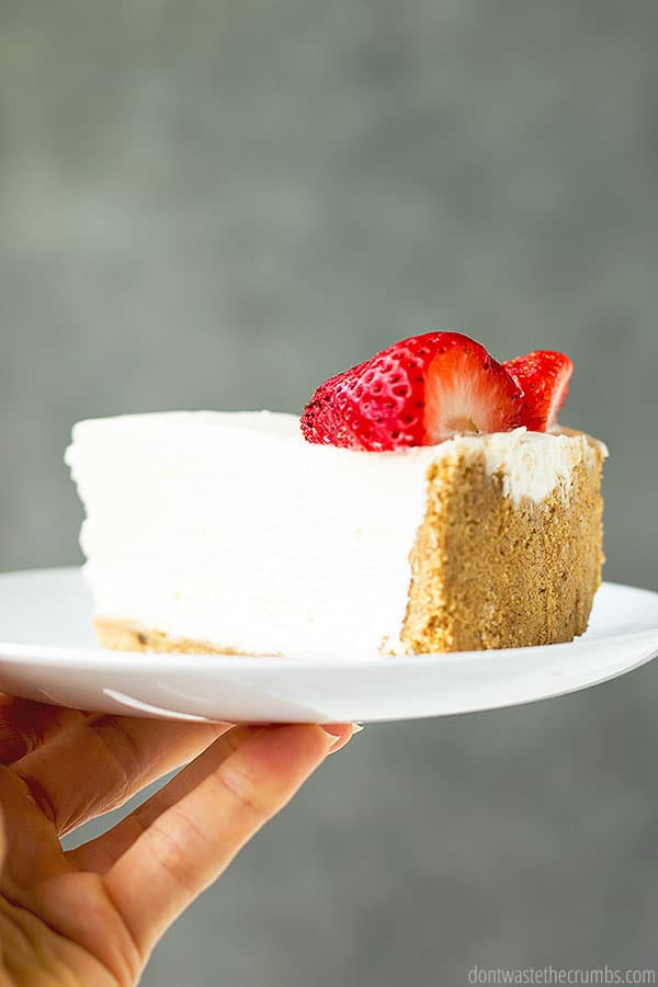 This slice of no-bake cheesecake   on a plate looks like a little piece of heaven just waiting to be devoured. The color contrast of the bright white, golden brown, and brilliant red is spectacular.