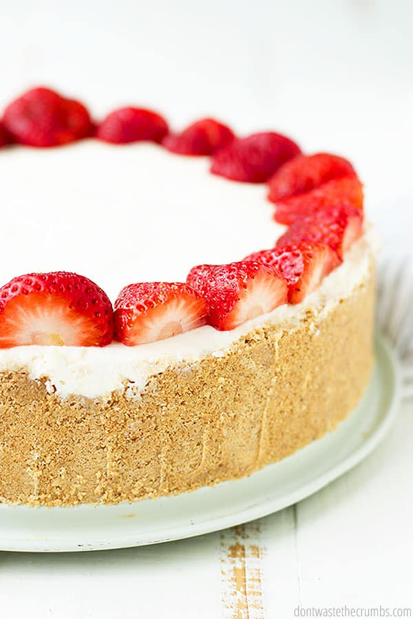 The finished cheese cake has a brown moist and crumbly crust with a white velvety filling, and sweet and sharp strawberries.