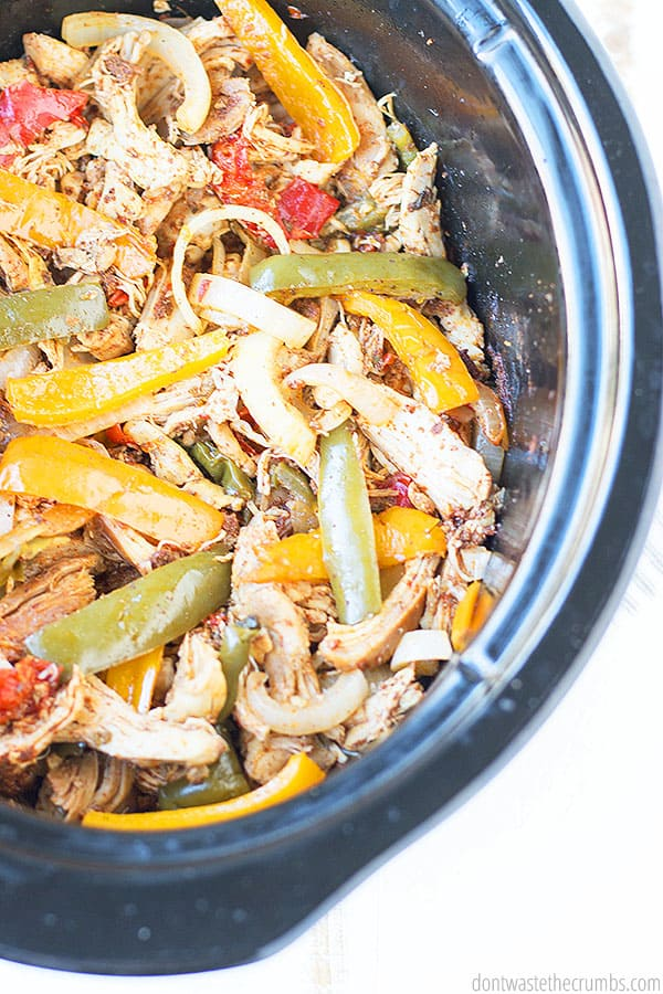 Cooked chicken, peppers, and, onions all seasoned and in a black slow cooker insert. The image is mouthwatering with the array of colors and potential flavor.