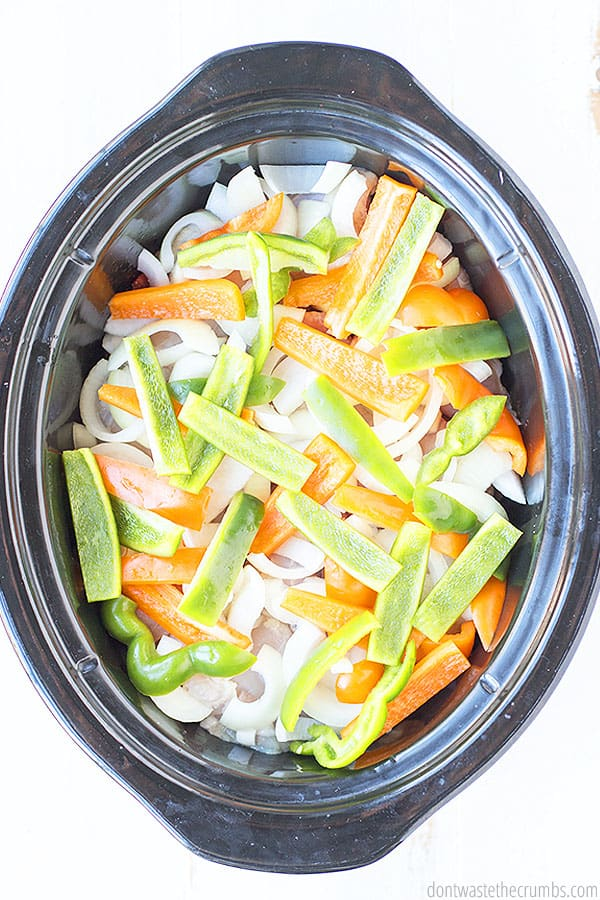 Fresh uncooked onions and peppers sliced up into stripes and placed in a slow cooker.  The bright white, orange, and green create a beautiful image.