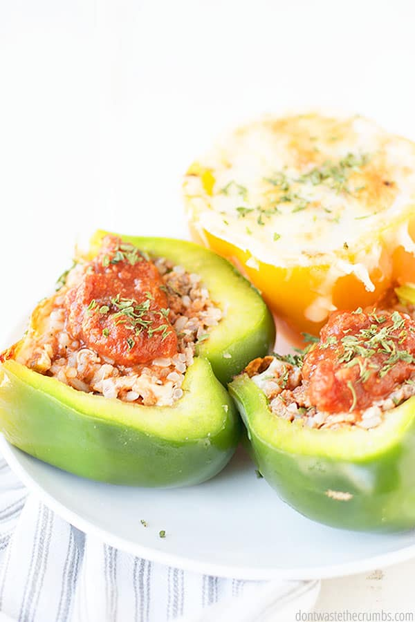 These stuffed peppers are delicious and budget friendly! These are the one of many cheap healthy meals that we have listed. They are placed on top of a plate.