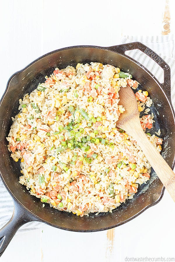 A large cast iron skillet with all of the delightful vegetable fried rice ingredients being stirred by a wooden spoon.