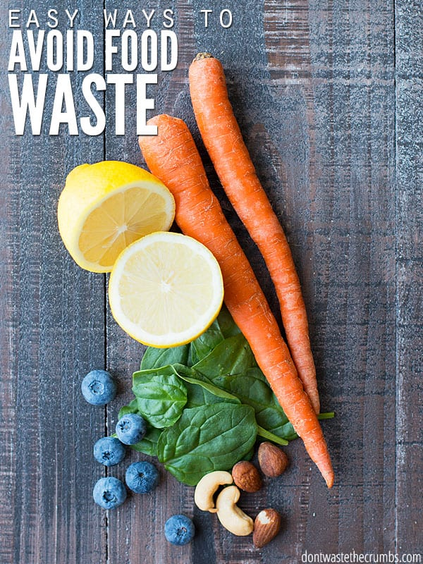 """Two bright orange carrots, a sliced lemon, a pile of spinach, six blueberries, and a handful of nuts. The text overlay says """"Easy Ways to Avoid Food Waste"""""""