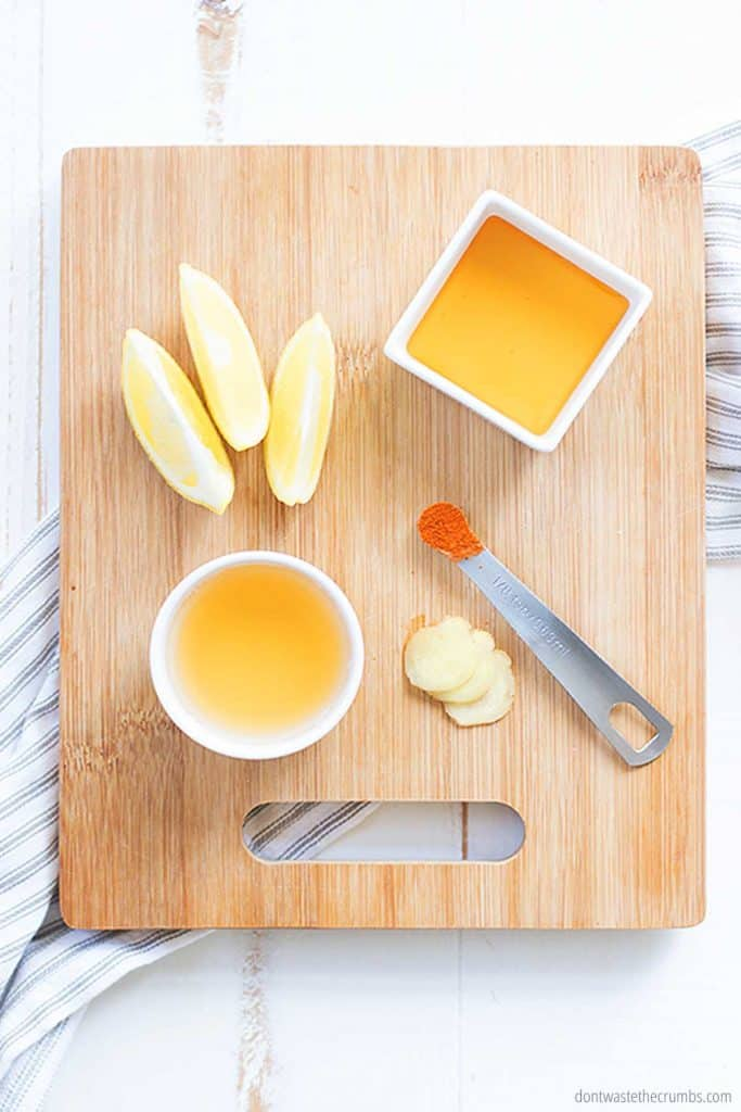 This homemade apple cider vinegar detox drink only needs apple cider vinegar, lemon juice, ginger, raw honey, and cayenne. All the ingredients are laid out on a cutting board in preparation for this healthy elixir.
