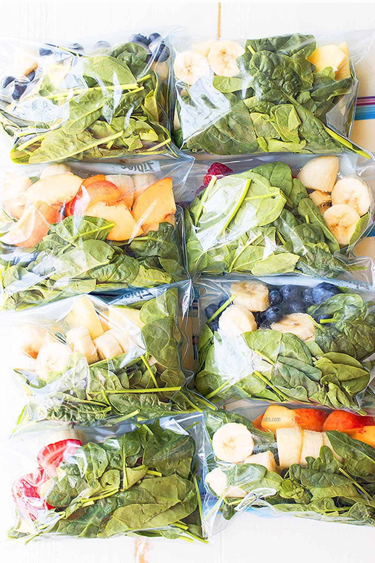 Finished smoothie packs are filled with many different fruits and vegetables (bananas, peaches, mangoes, strawberries, blueberries and greens) and ready to be frozen. The quart size freezer bags are lined up on the countertop, two in a row, with four rows of packs.