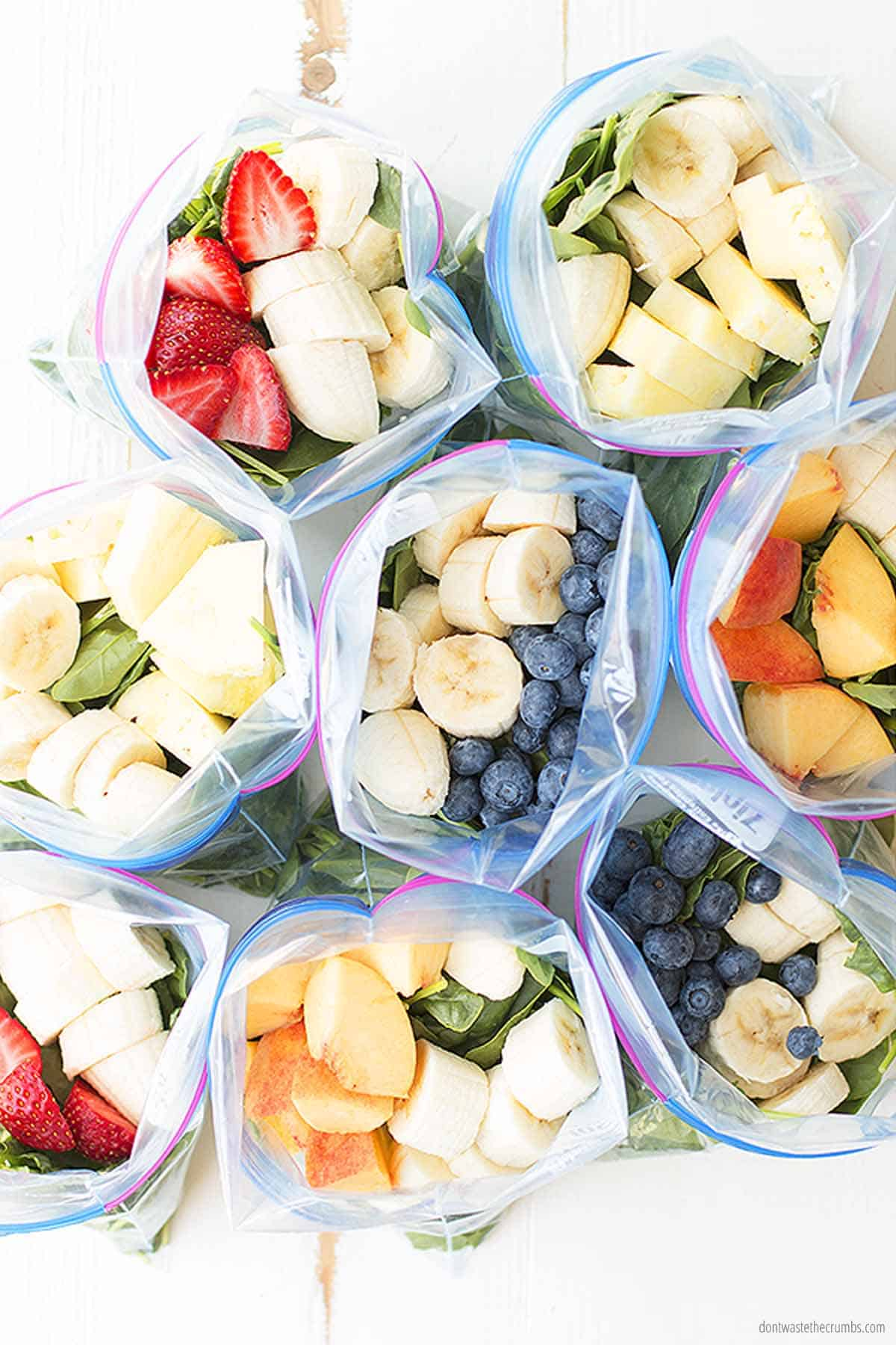 Eight freezer bags with mixed fresh fruits and greens, like strawberries, blueberries, bananas, peaches, and greens like spinach and baby kale. These filled freezer bags are ready to be frozen into freezer smoothie packs.