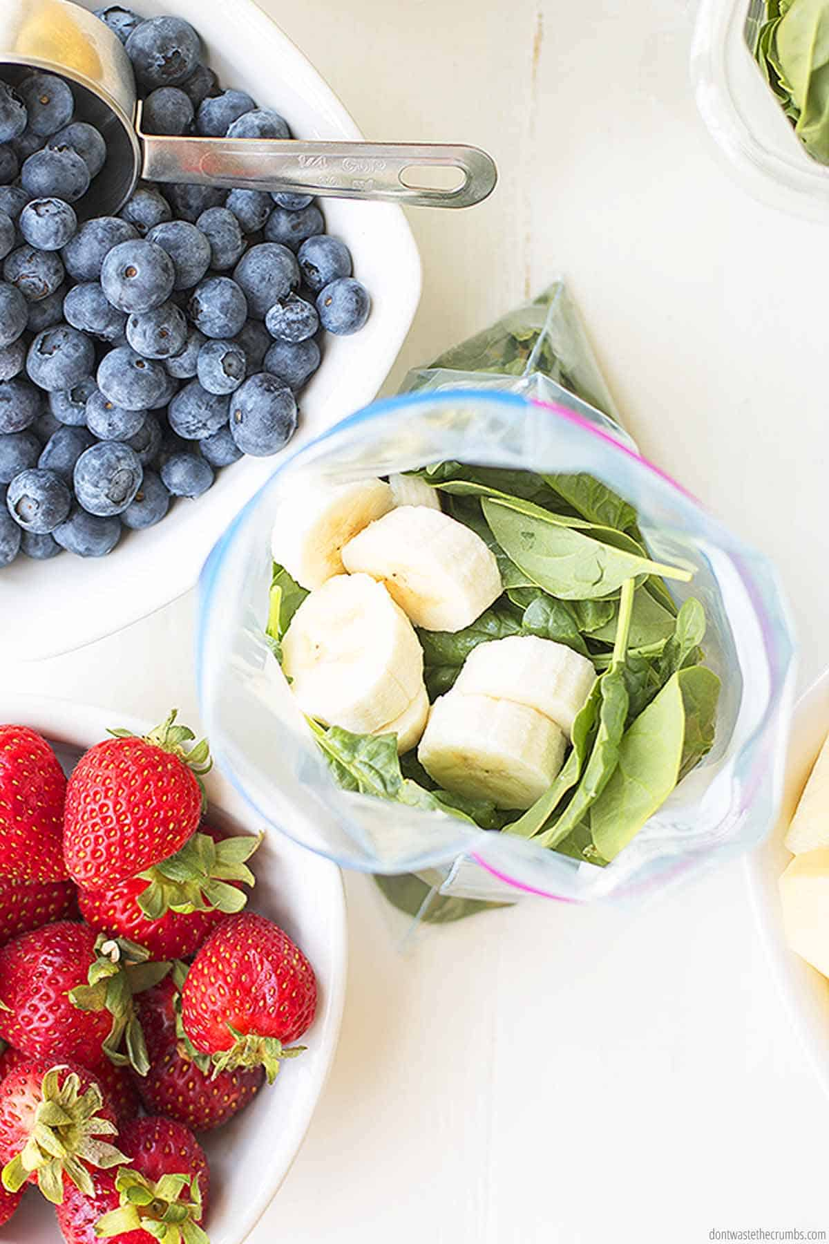 A freezer bag is being filled with fresh leafy greens and bananas. A bowl of blueberries has a stainless steel scoop inside of it. and there is a fresh bowl of strawberries as well.