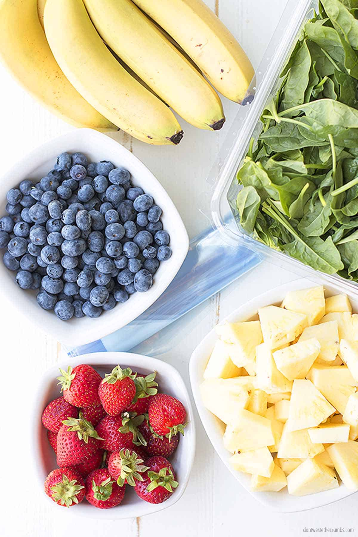 Five separate fresh fruit ingredients ready to be added to smoothie packs. There is a bowl of blueberries, strawberries, pineapple, and kale. There is also an unpeeled bunch of bananas.