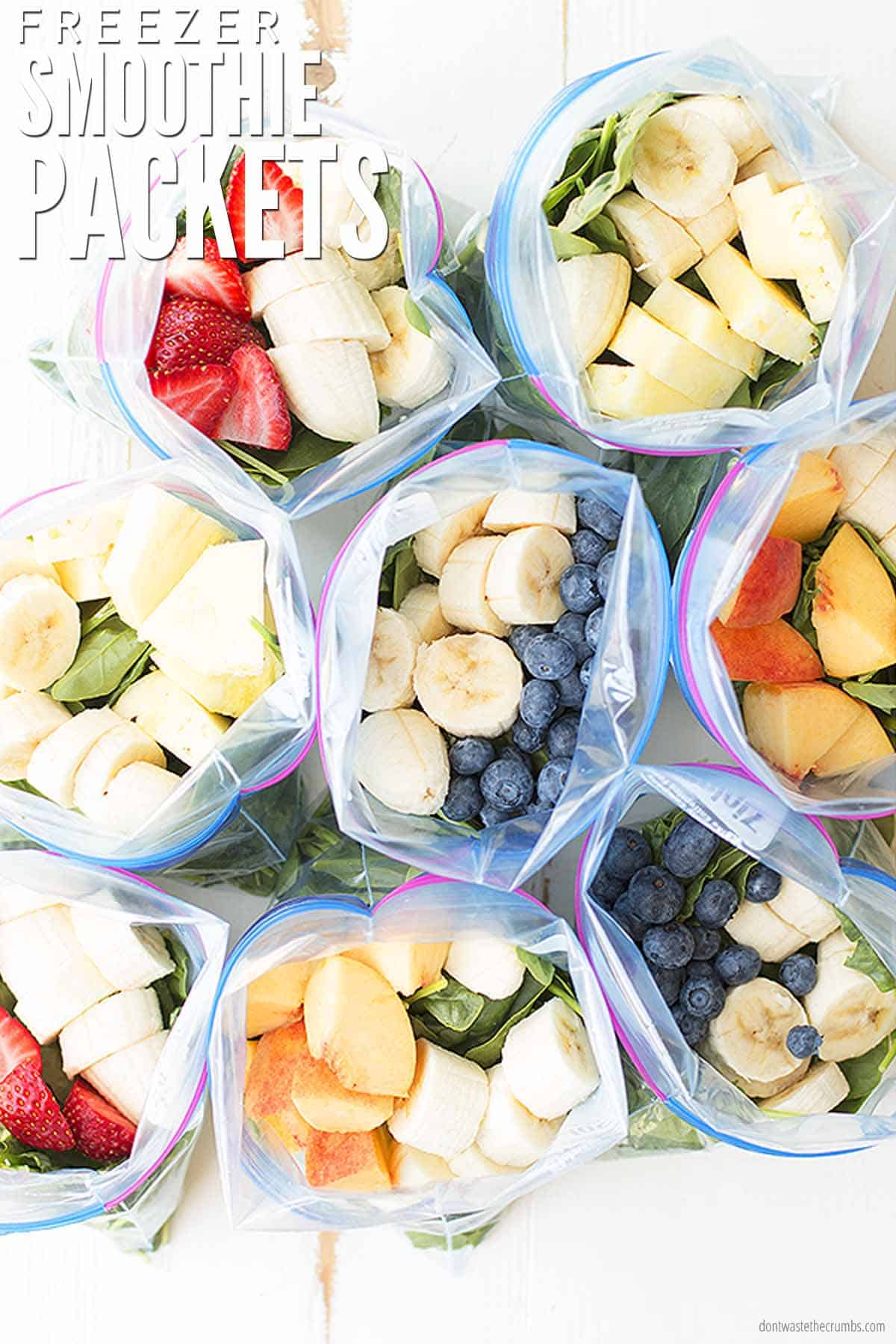 Eight freezer bags with mixed fresh fruits and vegetables, like strawberries, blueberries, bananas, mangoes, and greens like spinach and kale. They are ready to be frozen into freezer smoothie packs. The text overlay reads, 'Freezer Smoothie Packs.""