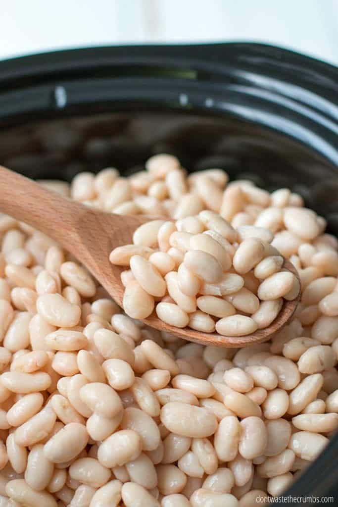 A wooden spoon full of slow cooked white beans inside of a black oval crockpot.