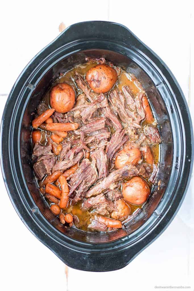 Delicious slow cooked chuck roast is bathed in it's natural juices with perfectly cooked carrots and potatoes. This slow cooker pot roast is ready to be served right out of a black oval slow cooker.