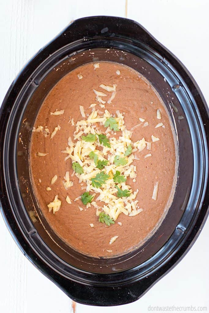 This crock pot refried beans dish is better than the store bought canned version. Topped with shredded cheese and cilantro. Try this easy recipe today!