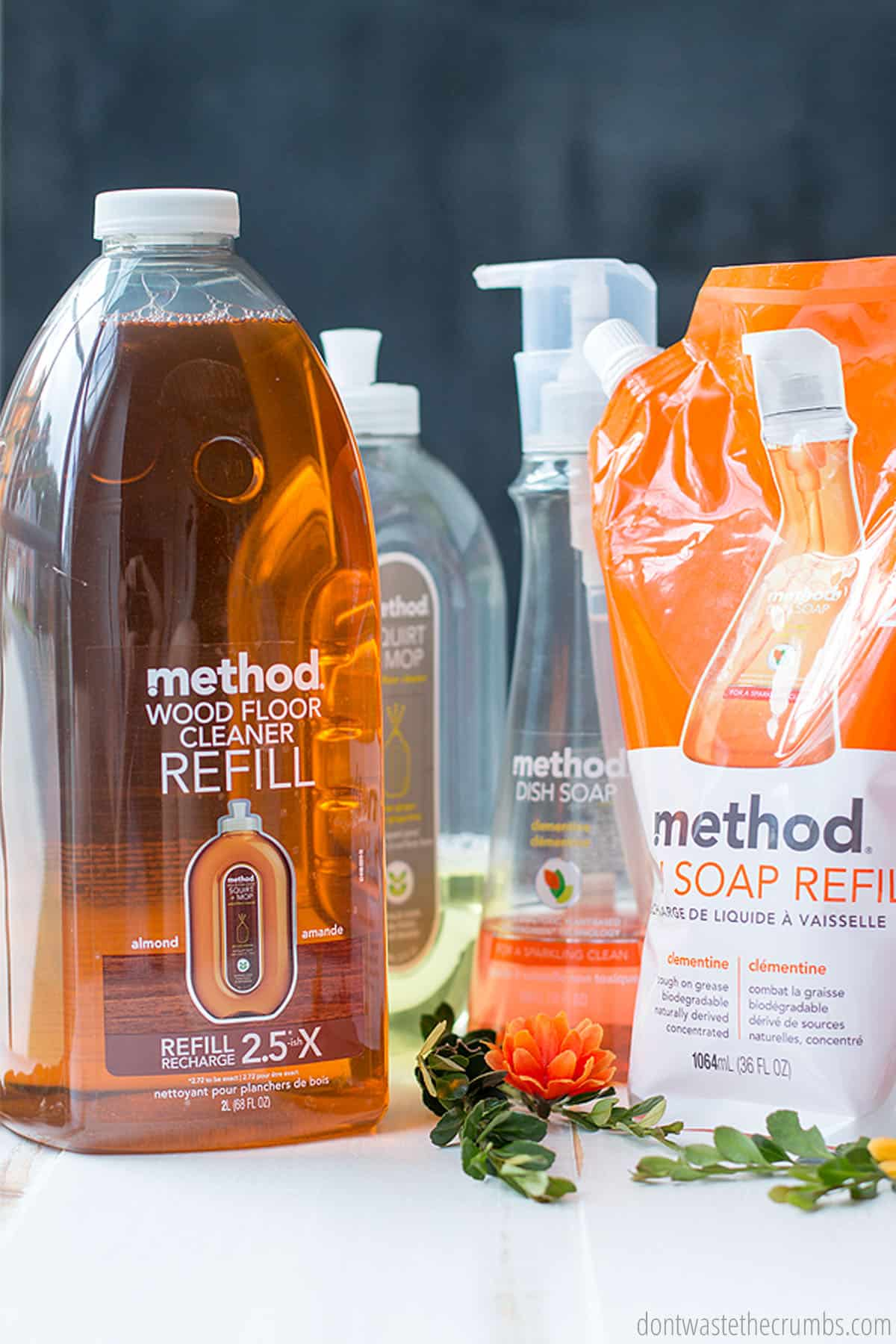 Method refill products are a great option at Grove Co. Pictured are a wood floor cleaner refill and a dish soap refill on a table beside some green leaves and stems.
