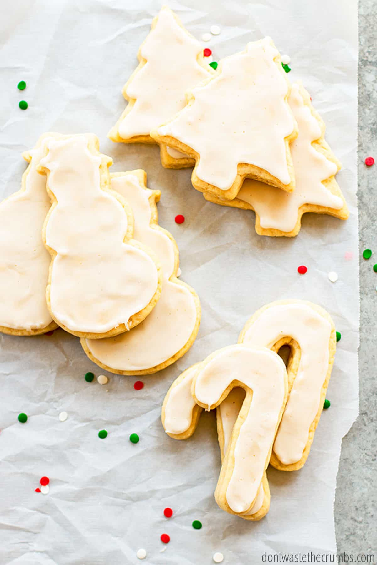 Nine Christmas cookies in the shapes of canes, snowmen and Christmas tree are fully iced and decorated - sitting on top of parchment paper on a granite countertop.