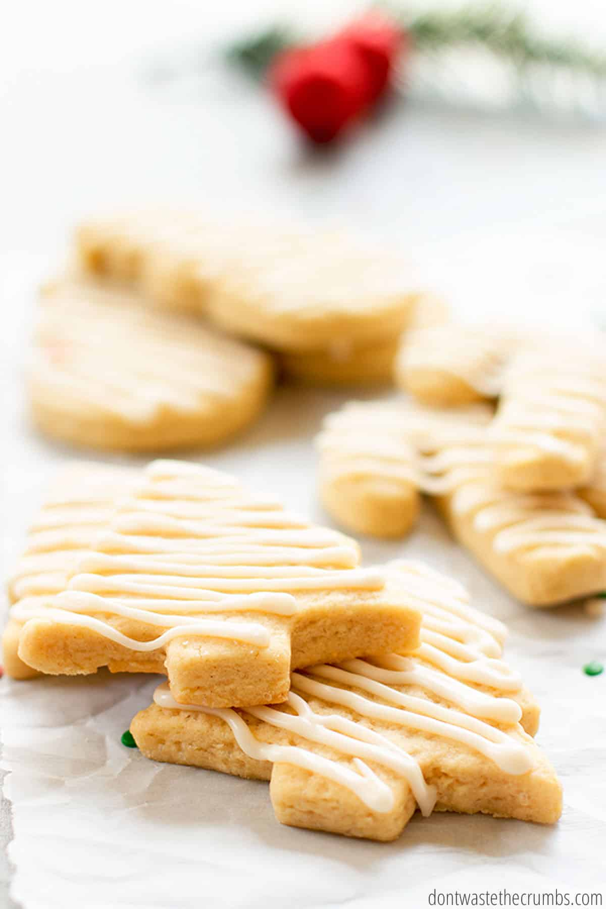 The zigzag iced sugar cookies, in the shape of Christmas trees, are stacked on top of each other. You can see how thick and chewy the cookies are from the side.