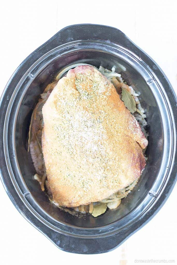 Now you will lay your pork roast on top of the onions in your slow cooker.