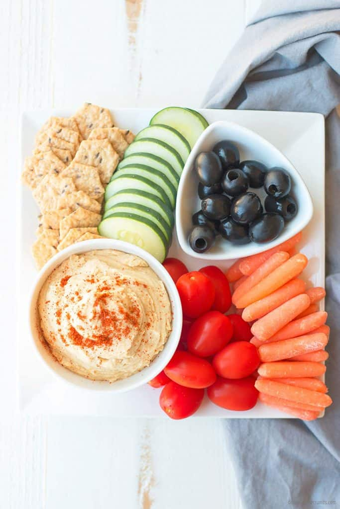 These homemade crackers, fresh cucumbers, carrots, cherry tomatoes, and olivesare all laid out beautifully around homemade hummus. Dig in!