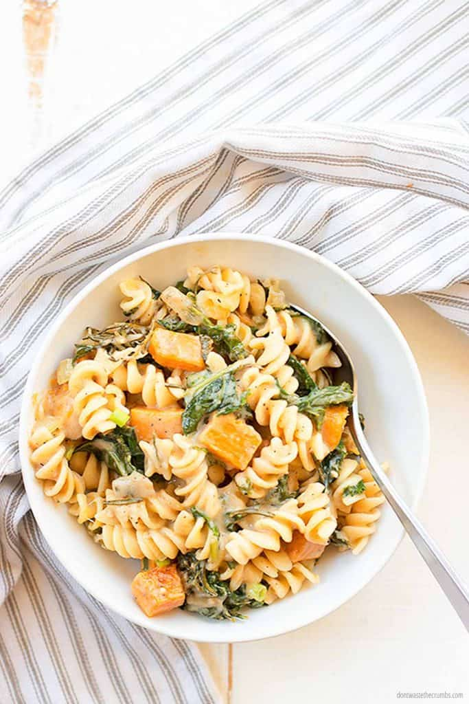 This Savory bacon, onion and greens pasta skillet id laid out on a plate, ready to eat. This fits perfectly in the weekly plan for $50.