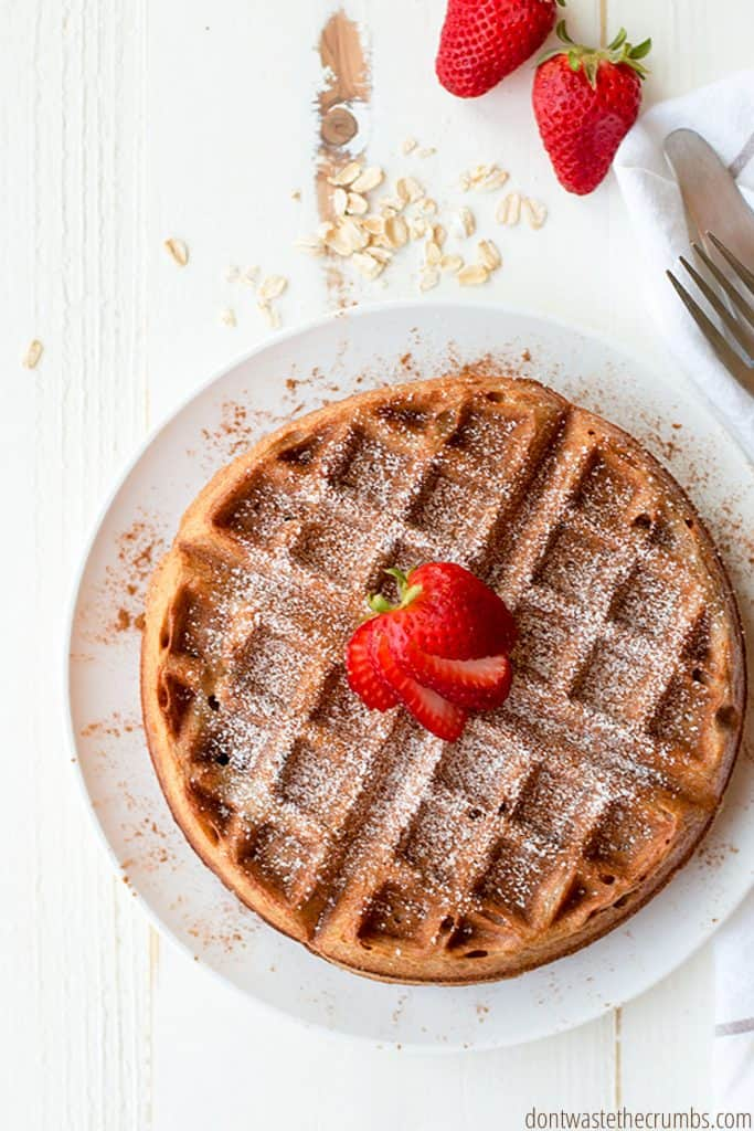 A freshly toasted cinnamon oatmeal waffle, golden brown, and dusted with ground cinnamon and powdered sugar. Fresh strawberries sit atop the waffles.
