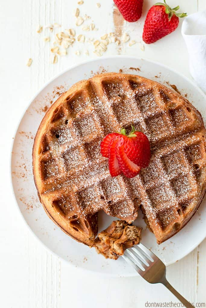 A round golden brown Belgian waffle topped with powdered sugar and sliced strawberries.
