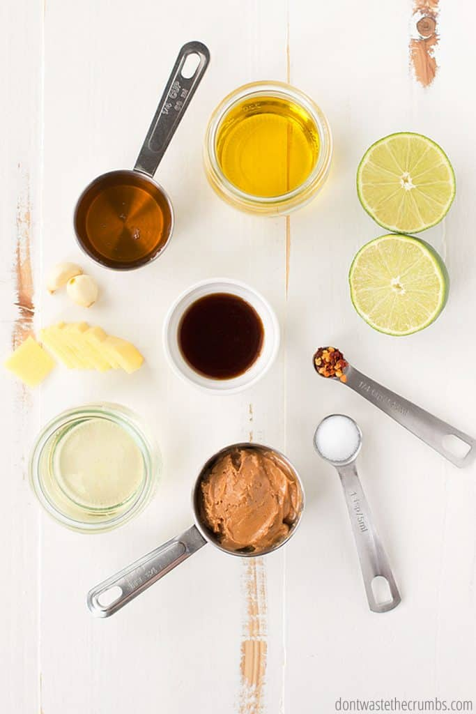Shown are all the measured ingredients needed for Thai peanut sauce: halved limes, honey, rice vinegar, soy sauce, garlic, sliced ginger, red pepper, salt, peanut butter, sugar, and maple syrup.