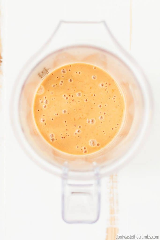 Thai peanut sauce is blended to a smooth and liquid-like consistency in the blender, pureed to a golden brown color.