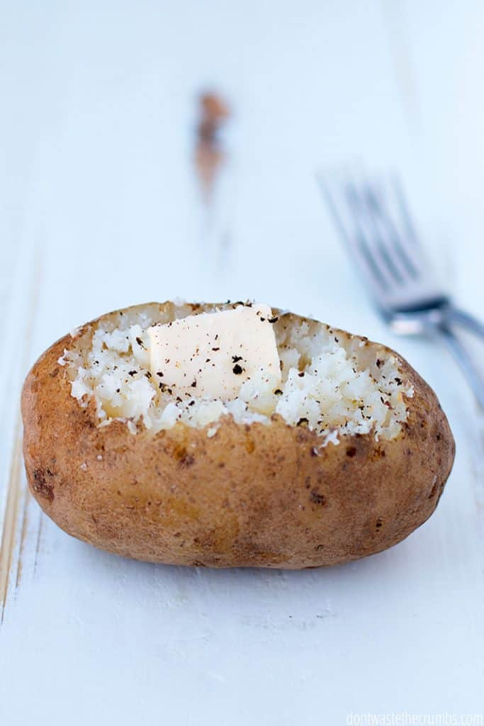 Perfectly baked potato seasoned with salt, pepper and a dollop of butter. The skin looks crispy and delicious.