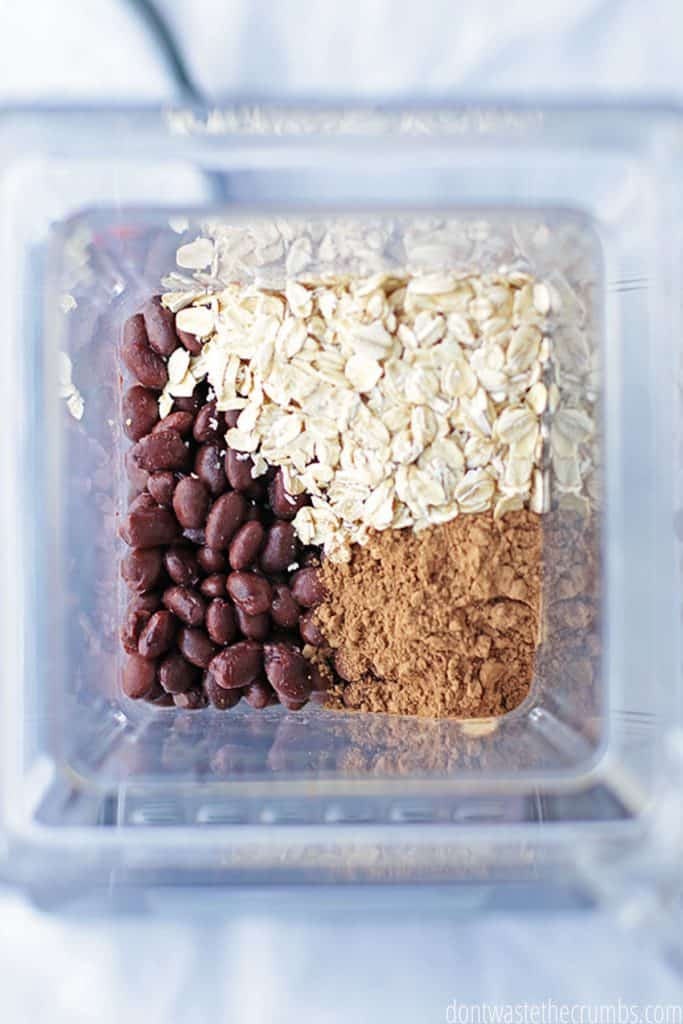 Ingredients for black bean brownies ready to be blended in a blender. There are black beans, cocoa, oats.'