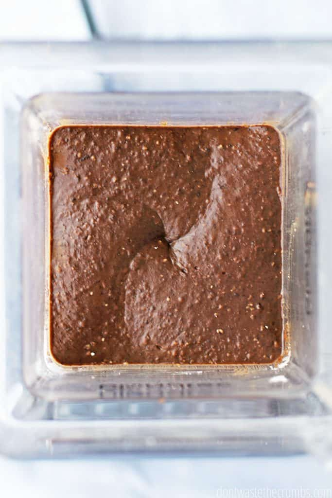 Black bean brownie ingredients are fully blended in the blender, resulting in a rich chocolatey texture.