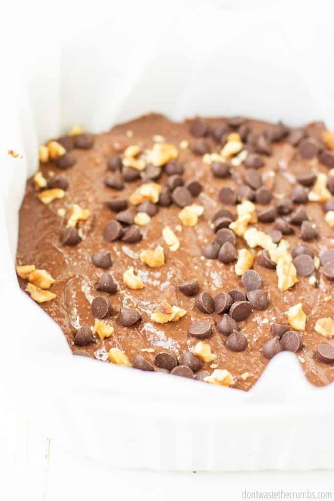 The black bean brownie batter is spread in the baking dish and topped with walnuts and chocolate chips - ready for baking!