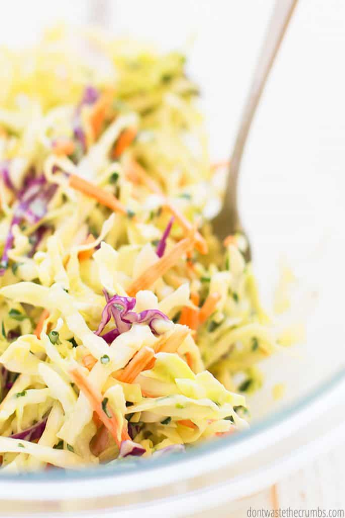 Cilantro lime coleslaw fills a clear bowl. Green cabbage is punctuated by slices of red cabbage, shredded carrots, and pieces of green onion and cilantro.