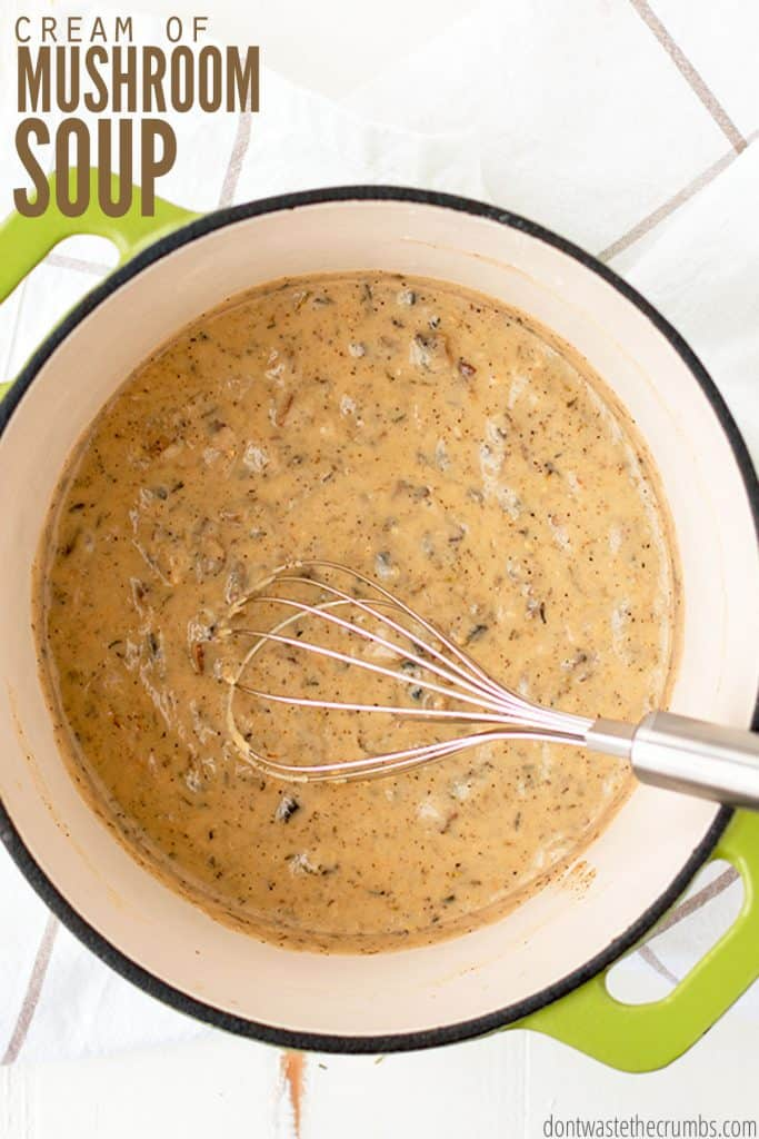 """A fresh pot of homemade cream of mushroom soup inside of a dutch oven pot with a whisk inside. The text overlay reads """"Cream of Mushroom Soup."""""""