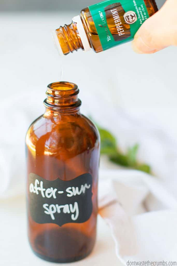 Peppermint essential oil drops are being poured into a glass bottle mister. This is one of the steps in order to make after sun spray.