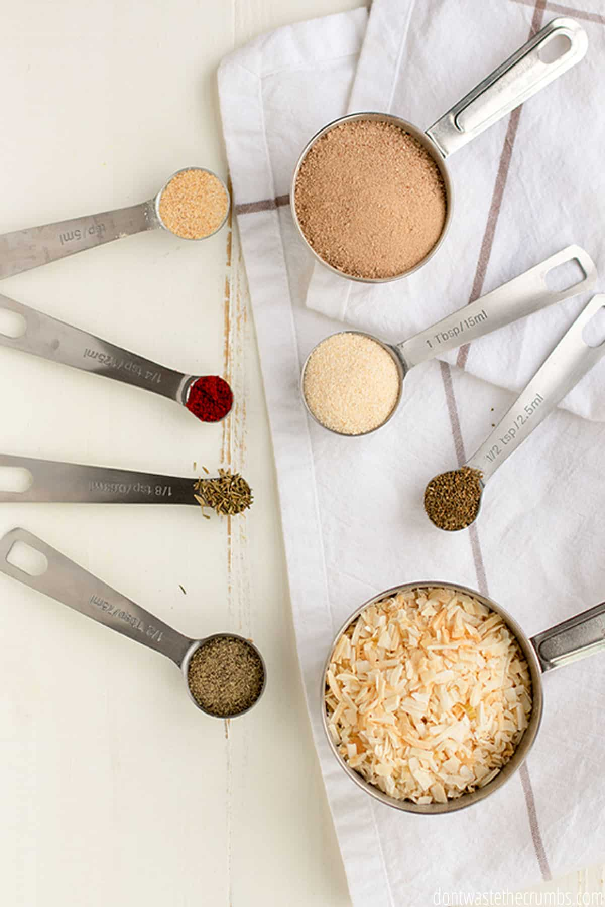 Eight measuring spoons with each of the ingredients used in a homemade dry onion soup mix recipe (granulated onion, onion powder, celery seed, beef bullion, garlic powder, paprika, salt, pepper, sugar.