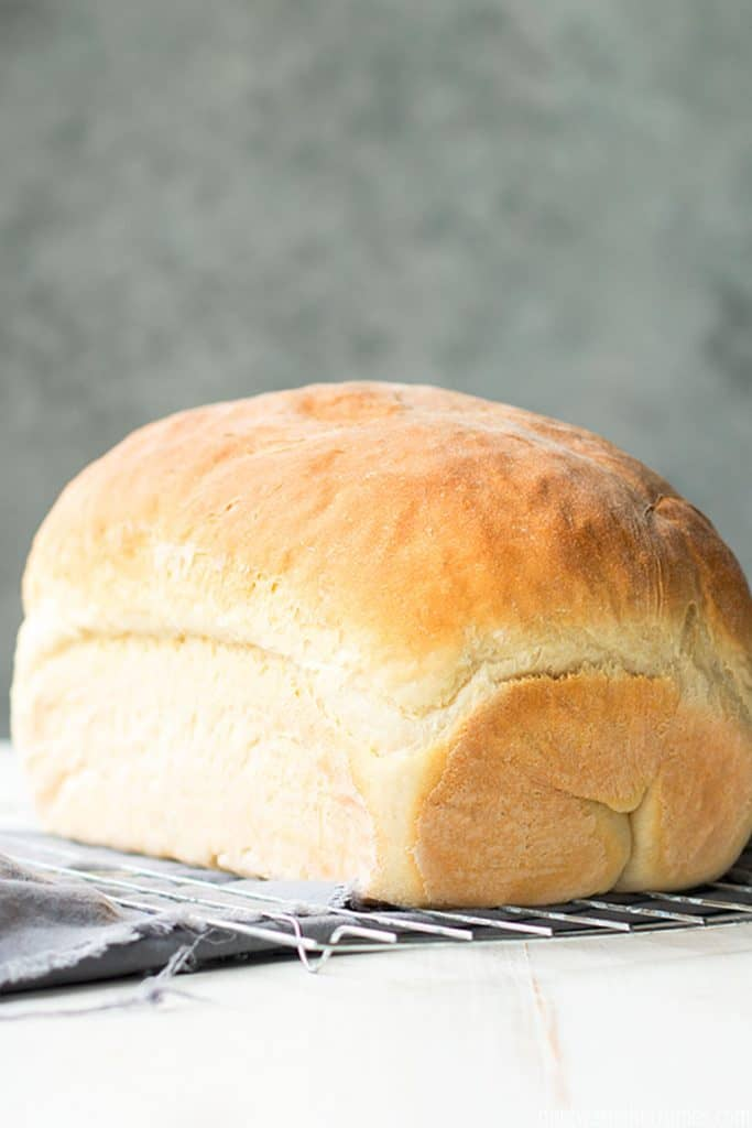 A fully baked whole loaf of white sandwich bread cooling on a cooling rack.