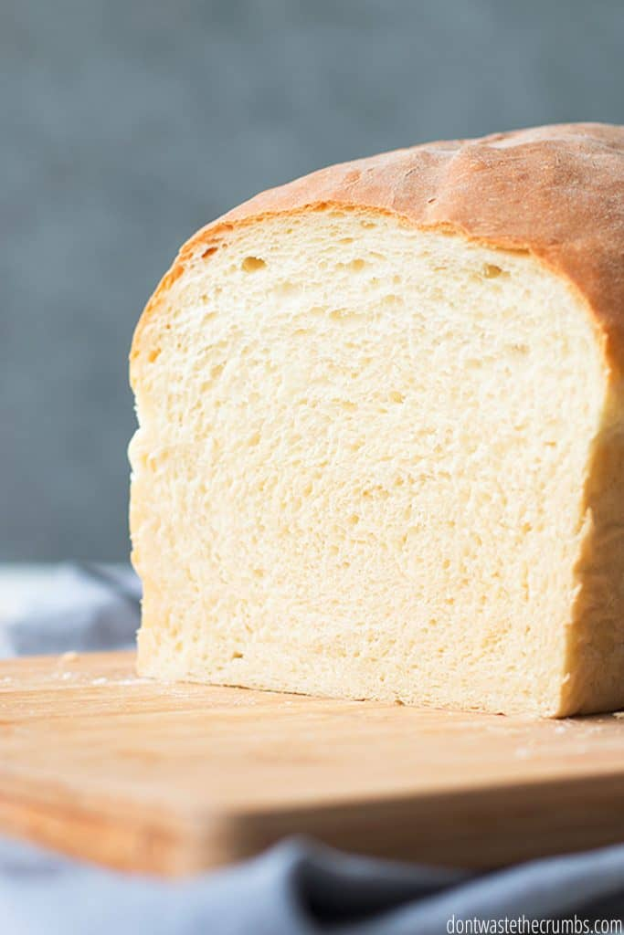A whole loaf of homemade bread sliced to show the fluffy white interior.
