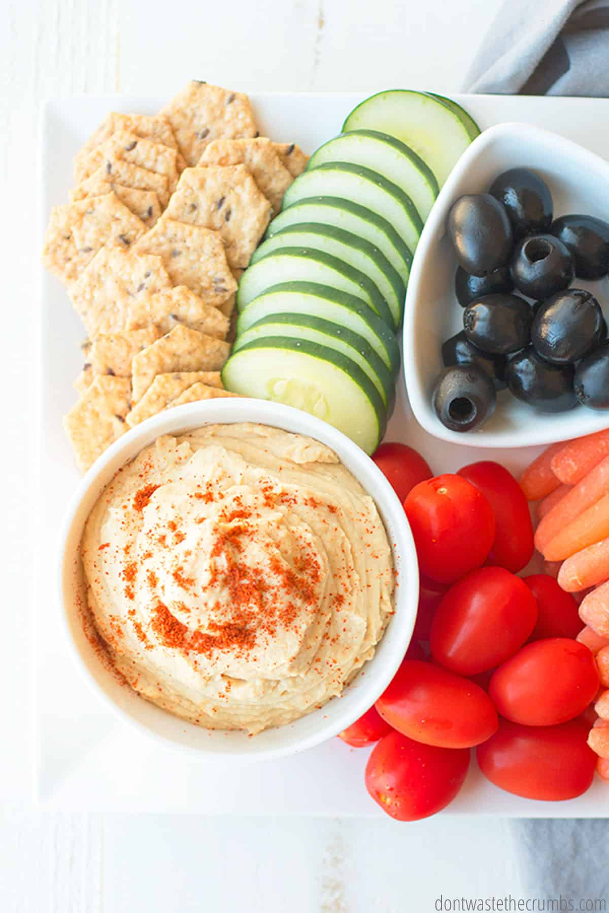 A small bowl of hummus finished with a sprinkle of cayenne pepper. Fresh tomatoes, carrots, cucumbers, olives and crackers are placed beside the dish for dipping.